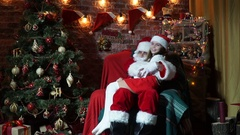 Santa Claus is shakes her the child in his knees Stock Footage