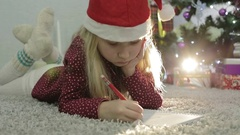 Baby girl in Santa hat and warm knitted socks lies on the floor and wrote a lett Stock Footage