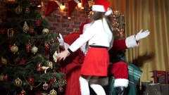 Little elf runs up and sits on her knees Santa Stock Footage