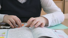 Schoolboy flips pages of textbook indoors Stock Footage