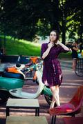 Fashion woman in checkered dress posing and pulling her hair near scooter over Stock Photos