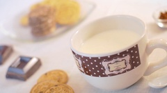 A woman hand dunks a cookie in the milk mug. Camera slider shot Stock Footage