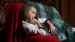 Sweet girl in plaid evening sitting in a chair Stock Footage