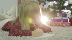 Child girl is thinking what to write Santa. Stock Footage