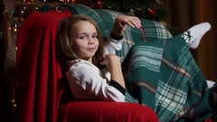 Girl smiling and flirting and wrapped in a blanket waving foot Stock Footage