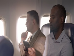 African American passenger using mobile device on commercial flight 4K Stock Footage