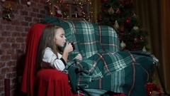 Girl drinking tea and having fun in a chair near a Christmas tree Stock Footage