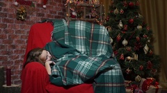 Girl wakes up in a chair near the Christmas tree Stock Footage