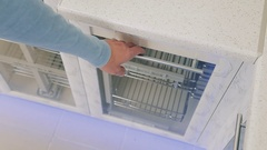 The hand of a young man is opening a furniture freezer door on kitchen in modern Stock Footage