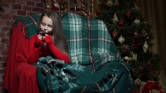 Girl in a red sweater on a chair drinking tea Stock Footage