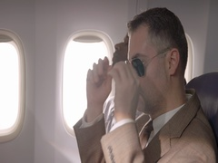 Airline passenger takes off sunglasses in main cabin of commercial flight 4K Stock Footage
