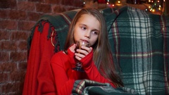 Girl in a red sweater thoughtfully sits with a cup of tea Stock Footage