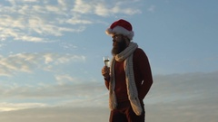 Slow motion: Santa pouring champagne and drinking alcohol after the party Stock Footage