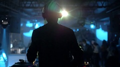 DJ turns the records at the club back view in modern nightclub Stock Footage