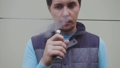 Man smoke electronic cigarette outdoor. Vaper. Steam. Slow motion. Stock Footage