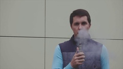 Young vaper man exhaling big clouds of smoke with e-cigarette vape slow motion Stock Footage