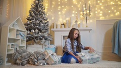 Little girl unties a bow on a box with a gift Stock Footage