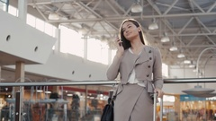 Happy young woman using smart phone in shopping mall. Businesswoman freelancer Stock Footage