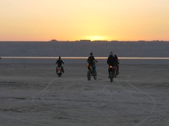 Bikers ride into sunset on lake, river, sea, bay. Man flees, falls and tumbles. Stock Footage