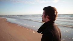 A young dark-haired man in a black coat is walking along the sea shore Stock Footage