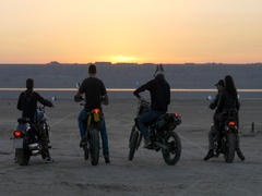 Bikers ride into sunset on lake, river, sea, bay. Motorcyclists passing desert. Stock Footage