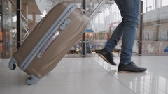 Young man pulling suitcase in modern airport terminal. Travelling guy wearing Stock Footage