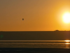 Balloon flying over the shore during gorgeous golden and orange sunset. Stock Footage