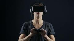 Virtual reality game. Man with pleasure uses head-mounted display in dark room Stock Footage