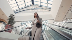Full length of confident businesswoman standing on escalator with laggage in Stock Footage