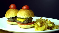 Small beef burgers with cereals bread, melted cheese, vegetables, french fries Stock Footage
