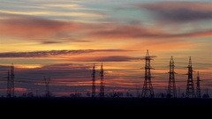 Beautiful sunset over field with silhouettes of electric poles-timelapse Stock Footage
