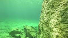 Move along underwater large rock with turquoise water Stock Footage