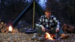 4K.Adult Man in hat  near bonfire make coffee. Autumn travel life.  Stock Footage