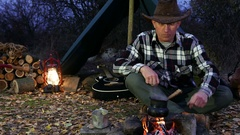 4K. Adult Man in hat  near bonfire make coffee. Autumn travel life.  Stock Footage