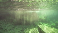 Sunrays penetrate underwater and lit volcanic rocks in slow motion Stock Footage