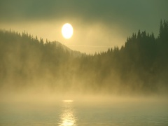 The sun rises over a mountain hill with fumes from lake-timelapse Stock Footage