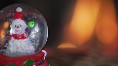 Snow ball of penguin close to a fireplace. Slow motion. Stock Footage
