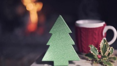 Christmas tree shape illuminated close to a red cup of coffee near fireplace. Stock Footage