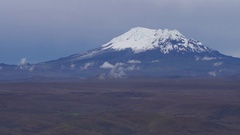 Pan along the Andes from a high viewpoint showing three volcanoes Stock Footage