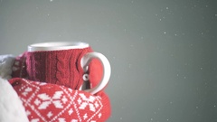 Warm up hands with red woolen mittens and a woolen cup of coffee or tea. Snow. Stock Footage