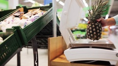 Woman weighing pineapple on scale at grocery store Stock Footage
