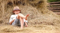 Little boy relaxing near the stack of hay Stock Footage