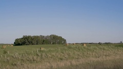 Pan right to left of hay bails in field behind wire fence in Manitoba Stock Footage