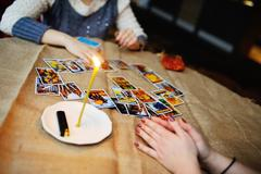 Divination by the Tarot cards. The fortune teller predicts the f Stock Photos