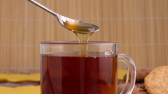 Honey pouring from spoon in hot tea. Transparent glass teacup in close up. Stock Footage