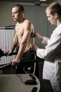 Athletic man with cardiogram electrodes on a treadmill Stock Photos