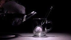Pouring hot water in glass teacup from transparent teapot. Stock Footage