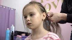 Hairdresser plaiting braids for little girls brunette Stock Footage