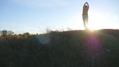 Young man practicing yoga moves and positions at hill at sunset. Slow motion Stock Footage