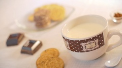 A woman hand dunks a cookie in the milk mug during the breakfast Stock Footage